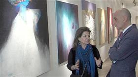 الفنانة التشكيلية شيخة سنان امام احدى لوحاتها في معرض الفنون التشكيلية بالقاهرة