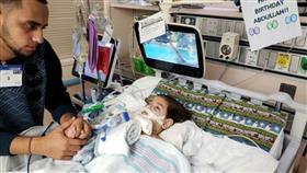 """صورة الطفل عبد الله حسن بمستشفى """"يو سي اس اف بينيوف"""" للأطفال في أوكلاند وبجانبه والده"""