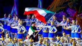 لاعب منتخب الكويت لألعاب القوى عيسى الزنكوي يحمل علم الكويت