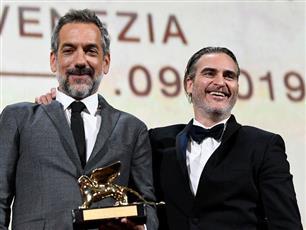 المخرج تود فيليبس يقف بجانب جواكين فينيكس بعد فوزه بجائزة الأسد الذهبي لأفضل فيلم