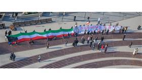 فنانون تشكيليون يحملون أطول علم للكويت وأطول لوحة باسم «قائد الإنسانية»